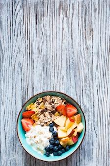 Pequeno-almoço saudável com frutas e cereais em madeira rústica