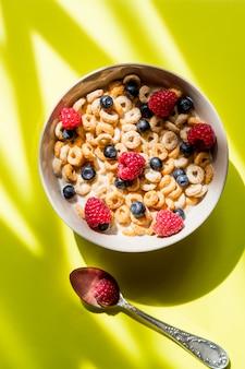 Pequeno-almoço saudável com frutas, frutos secos, nozes, cereais. flocos de milho com framboesas e mirtilos na parede amarela. flocos de milho doces com frutas e leite como refeição saudável
