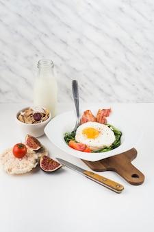 Pequeno-almoço saudável com garrafa de leite; flocos de milho; biscoito de figo e arroz contra o pano de fundo texturizado mármore