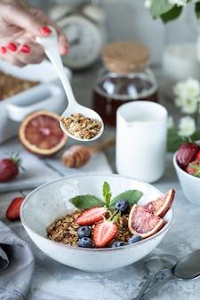 Pequeno-almoço saudável com granola, iogurte, frutas, bagas em um prato branco em chapa branca.