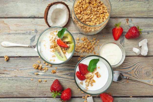 Pequeno-almoço saudável com iogurte, frutas e granola na vista superior da mesa de madeira