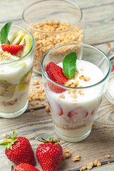 Pequeno-almoço saudável com iogurte, frutas e granola na vista superior de mesa de madeira