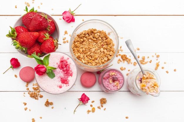 Pequeno-almoço saudável com iogurte, granola e morangos na vista superior de madeira branca