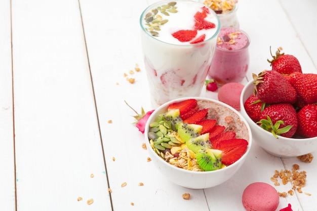 Pequeno-almoço saudável com iogurte, granola e morangos na vista superior do fundo de madeira branco