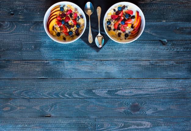 Pequeno-almoço saudável com leite, cereais e frutas, numa superfície de madeira.