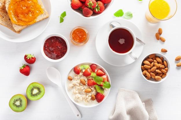 Pequeno-almoço saudável com mingau de aveia, morango, nozes, torradas, geléia e chá. vista do topo