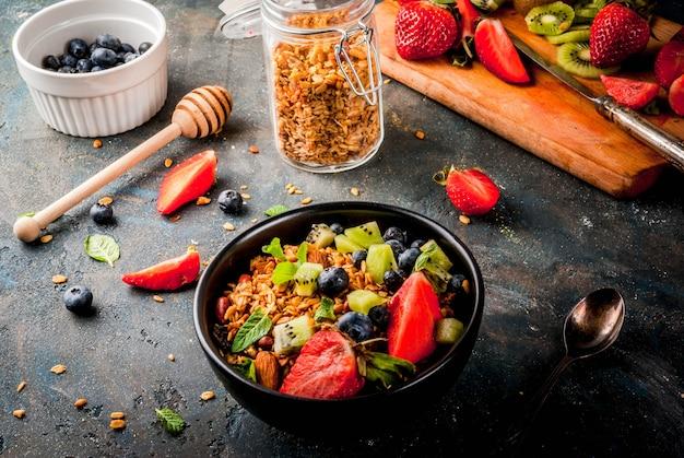 Pequeno-almoço saudável com muesli ou granola com nozes e frutas frescas e frutas - morango, mirtilo, kiwi, na mesa azul escura, copyspace