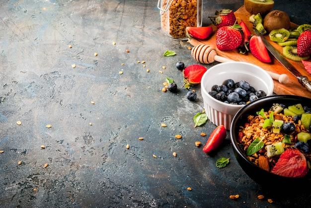 Pequeno-almoço saudável com muesli ou granola com nozes e frutas frescas e frutas morango mirtilo kiwi na mesa azul escura