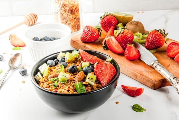 Pequeno-almoço saudável com muesli ou granola com nozes e frutas frescas e frutas - morango, mirtilo, kiwi, na mesa branca, copyspace