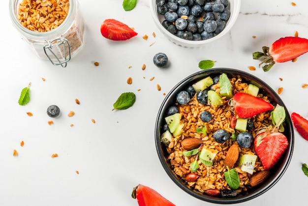 Pequeno-almoço saudável com muesli ou granola com nozes e frutas frescas e frutas morango mirtilo kiwi na vista superior de mesa branca