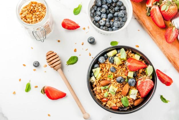 Pequeno-almoço saudável com muesli ou granola com nozes e frutas frescas e frutas - morango, mirtilo, kiwi