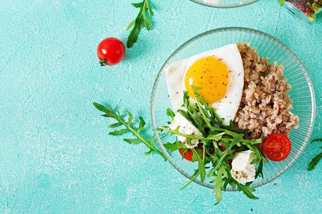 Pequeno-almoço saudável com ovo, queijo feta, rúcula, tomate e mingau de trigo sarraceno na luz de fundo. nutrição apropriada. cardápio dietético. postura plana. vista do topo