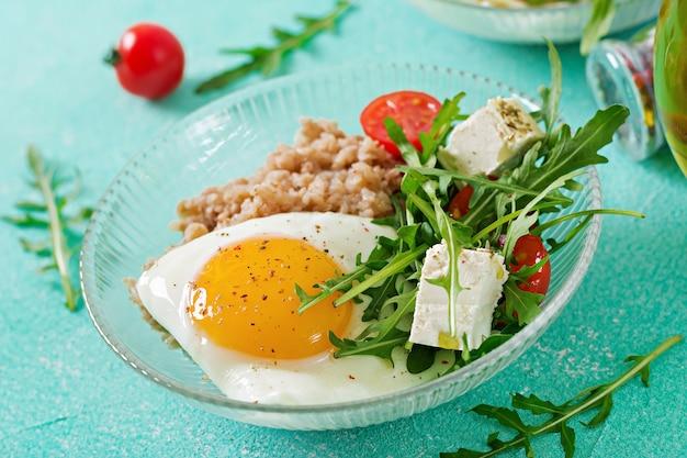Pequeno-almoço saudável com ovo, queijo feta, rúcula, tomate e mingau de trigo sarraceno na luz de fundo. nutrição apropriada. cardápio dietético.