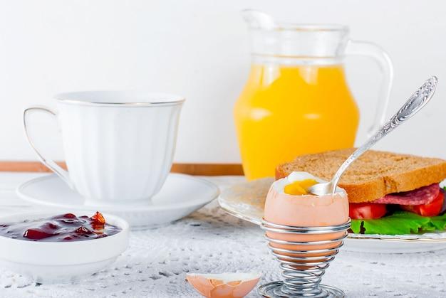 Pequeno-almoço saudável com ovo, sandviches, torradas, geléia e juce