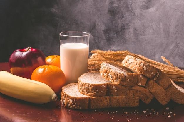 Pequeno-almoço saudável com pão integral, leite e frutas na mesa