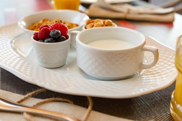 Pequeno-almoço saudável com suco fresco e muesli com leite e frutas