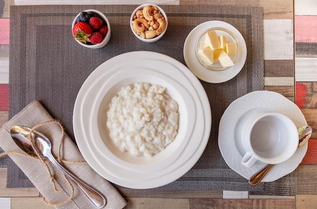Pequeno-almoço saudável com tigela de mingau de arroz com frutas e nozes em cima da mesa
