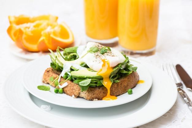 Pequeno-almoço saudável com torradas de pão integral e ovo escalfado