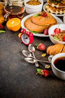 Pequeno-almoço saudável comer conceito, vários alimentos da manhã - panquecas, waffles, sanduíche de aveia croissant e granola com iogurte, frutas, bagas, café, chá, suco de laranja
