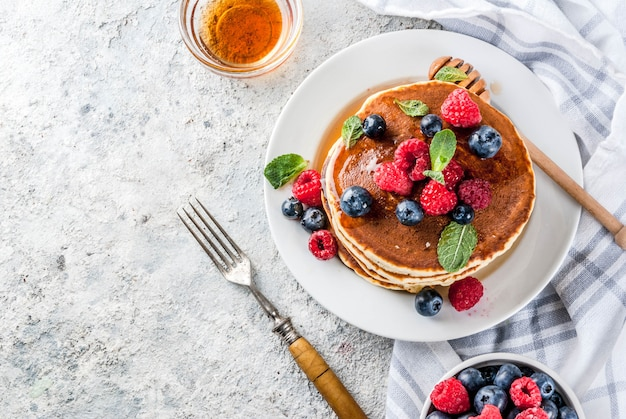 Pequeno-almoço saudável de verão, panquecas americanas clássicas caseiras com bagas frescas e mel, vista superior da superfície de pedra cinza claro de manhã