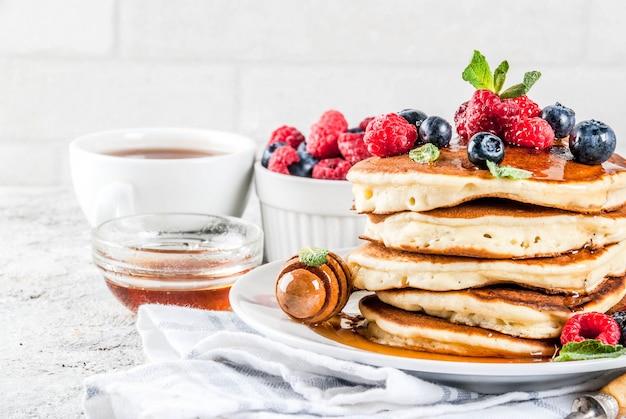 Pequeno-almoço saudável de verão, panquecas americanas clássicas caseiras com frutas frescas e mel, superfície de pedra cinza claro de manhã