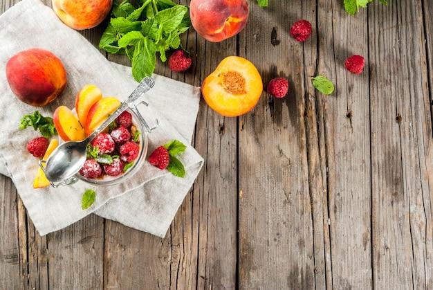 Pequeno-almoço saudável de verão. pernoite de aveia em uma jarra, granola, nozes, framboesas frescas e pêssego, decorado com folhas de hortelã. na velha mesa de madeira rústica. vista superior copyspace