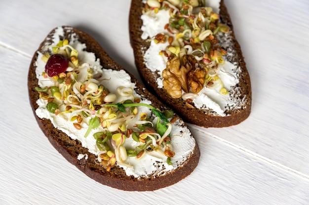 Pequeno-almoço saudável e macrobiótica. sanduíche com creme de queijo, ervilhas microgreens e brotou feijão mungo, nozes, girassol e linho em fundo de madeira. vegan, dieta de alimentos crus