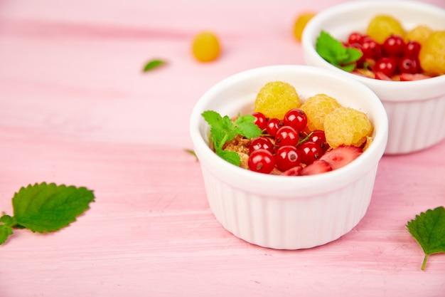 Pequeno-almoço saudável em tigelas brancas. granola fresca,