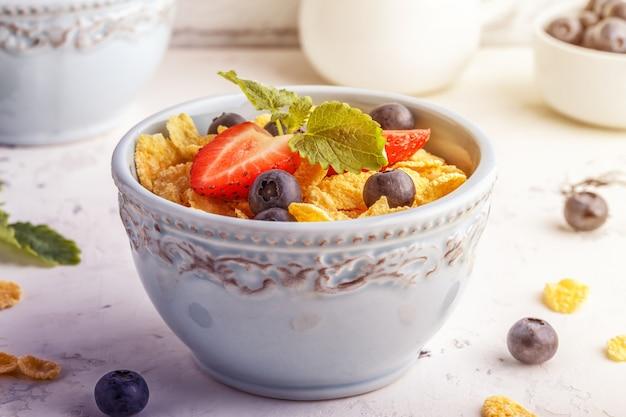 Pequeno-almoço saudável - flocos de milho com frutas e bagas.