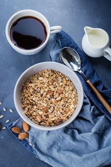 Pequeno-almoço saudável - granola, leite ou iogurte e mel na bandeja de madeira no fundo da mesa de pedra.