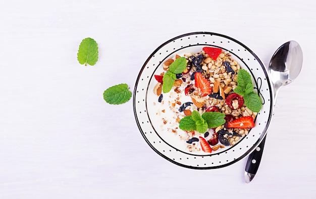 Pequeno-almoço saudável - granola, morangos, cereja, madressilva, nozes e iogurte em uma tigela