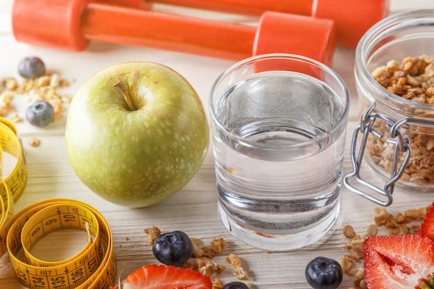 Pequeno-almoço saudável, halteres e fita métrica na mesa de madeira.