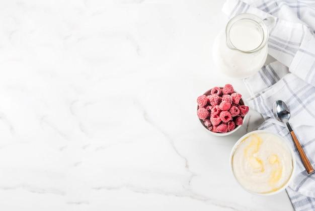 Pequeno-almoço saudável, mingau de sêmola com leite e framboesa, mesa de mármore branco