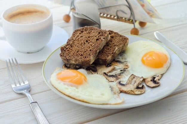 Pequeno-almoço saudável, ovos fritos com cogumelos e duas fatias de pão de centeio