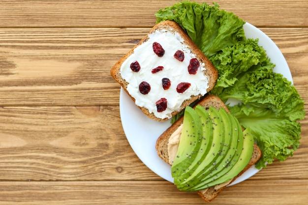 Pequeno-almoço saudável, pão integral com abacate, queijo feta e cranberries secas
