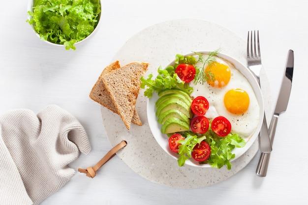 Pequeno-almoço saudável plana leigos. ovos fritos, abacate, tomate, torradas