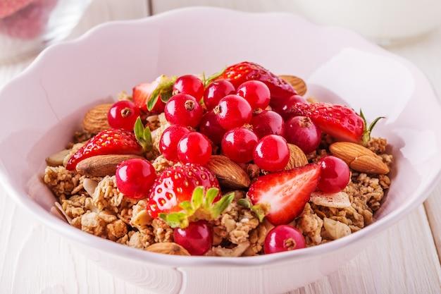 Pequeno-almoço saudável - tigela de granola de aveia com frutas frescas, amêndoa e chocolate branco.