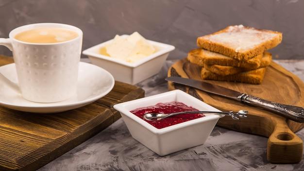 Pequeno-almoço simples de produtos tradicionais - torrada com manteiga e geléia de framboesa