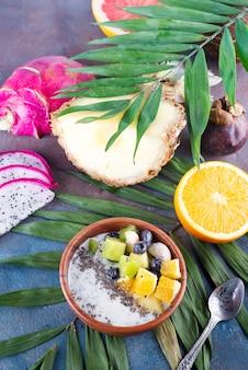 Pequeno-almoço smoothie tigela coberto com pitaya, abacaxi, sementes de chia e bagas com folha de palmeira sobre fundo de pedra, vista superior