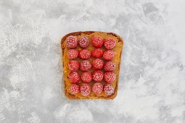 Pequeno-almoço tradicional americano e europeu de verão: sanduíches de torradas com manteiga de amendoim, amora, pêssego, figo, morango, framboesa, cópia, vista superior
