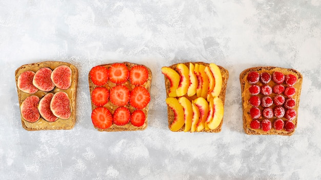 Pequeno-almoço tradicional americano e europeu de verão: sanduíches de torradas com manteiga de amendoim, copie a vista superior