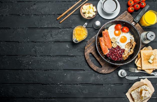 Pequeno-almoço tradicional inglês com ovos estrelados, enchidos e café aromático. na superfície preta rústica.