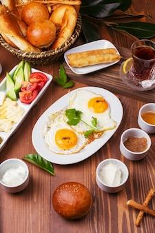 Pequeno-almoço turco com ovos fritos, tomate, pepino, variedades de queijo, azeitonas verdes pretas, mel, geléia, queijo creme, pão galeta e copo de chá