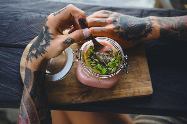 Pequeno-almoço útil. um belo café da manhã, as mãos dos homens em tatuagens.