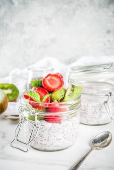 Pequeno-almoço vegan dietético saudável, iogurte com sementes de chia e frutas frescas, morangos, kiwi. espaço de cópia de fundo de mármore branco