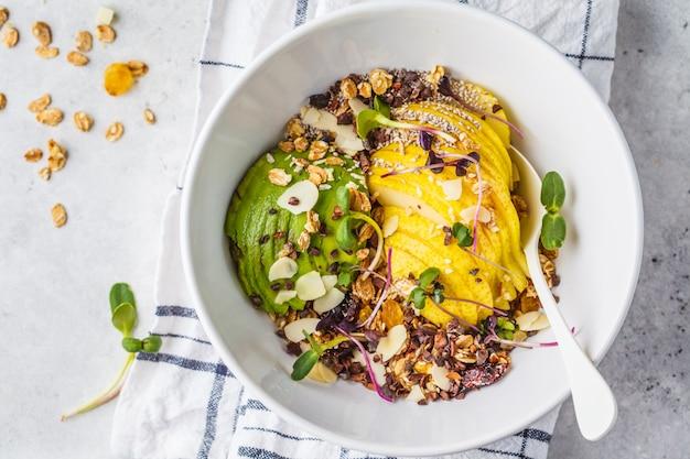 Pequeno-almoço vegan saudável. granola com abacate, superalimentos, frutas e frutas em uma tigela branca, vista superior.
