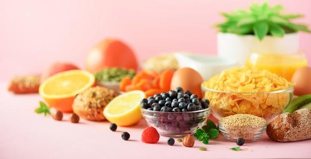 Pequeno-almoço vegetariano. ovo cozido, flocos de aveia, nozes, frutas, bagas, leite, iogurte, laranja, banana, pêssego no fundo rosa. dieta alimentar saudável. copie o espaço. bandeira