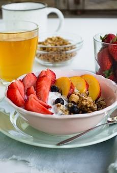 Pequeno-almoço vegetariano saudável. uma tigela de granola, frutas e frutas