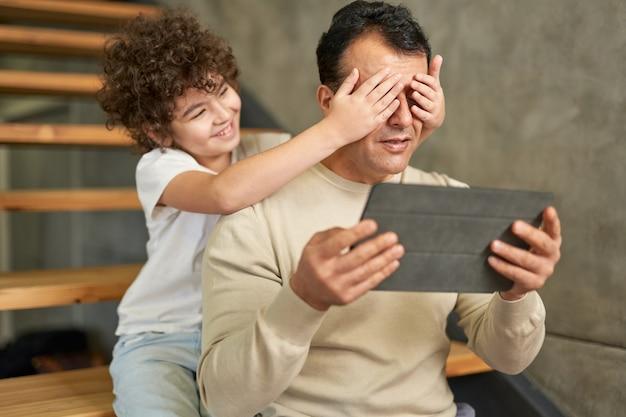 Pequeno assistente alegre menino de escola latina brincando com seu pai enquanto ele está segurando um tablet