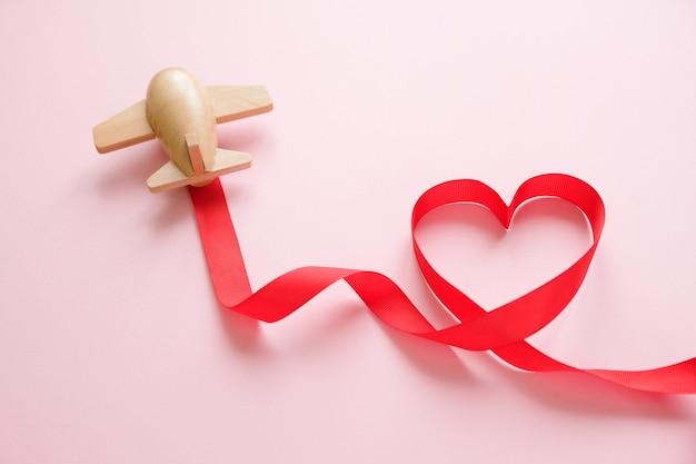 Pequeno avião de brinquedo de madeira carrega uma fita vermelha em forma de coração